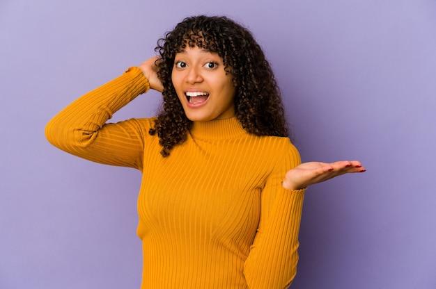 Młoda afro amerykańska kobieta na białym tle trzyma miejsce na dłoni, trzymaj rękę na policzku. zdziwiony i zachwycony.