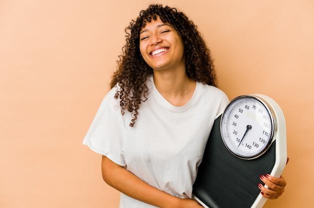 Młoda afro amerykańska kobieta trzyma wagi śmiechu i zabawy.