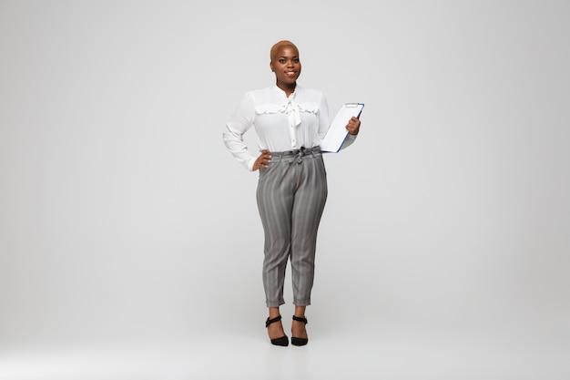 Młoda afro-amerykańska kobieta w szarym stroju casual
