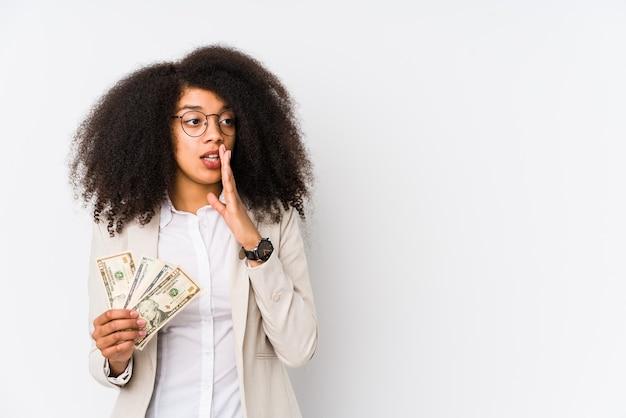 Młoda afro biznesowa kobieta trzymająca samochód na kredyt na białym tle młoda afro biznesowa kobieta trzymająca kredytowy caris, mówiąca tajną gorącą wiadomość o hamowaniu i patrząc na bok