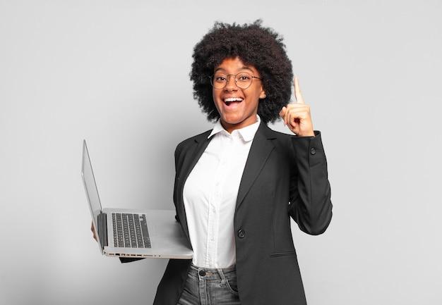 Młoda afro bizneswoman czując się jak szczęśliwy i podekscytowany geniusz po zrealizowaniu pomysłu, radośnie unosząc palec, eureka!. pomysł na biznes