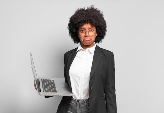 Młoda afro bizneswoman czuje się smutna i marudna z nieszczęśliwym spojrzeniem, płacze z negatywnym i sfrustrowanym nastawieniem. biznes