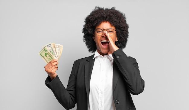 Młoda afro bizneswoman czuje się szczęśliwa, podekscytowana i pozytywna, wydając wielki okrzyk z rękami przy ustach, wołając. pomysł na biznes