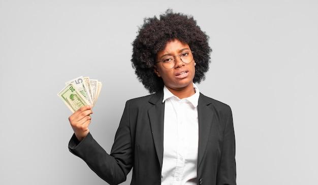 Młoda afro bizneswoman czuje się zakłopotana i zdezorientowana, z tępym, oszołomionym wyrazem twarzy, patrzącą na coś nieoczekiwanego. pomysł na biznes
