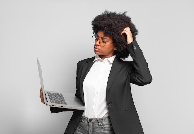 Młoda afro bizneswoman czuje się zdziwiona i zdezorientowana, drapiąc się po głowie i patrząc w bok. pomysł na biznes