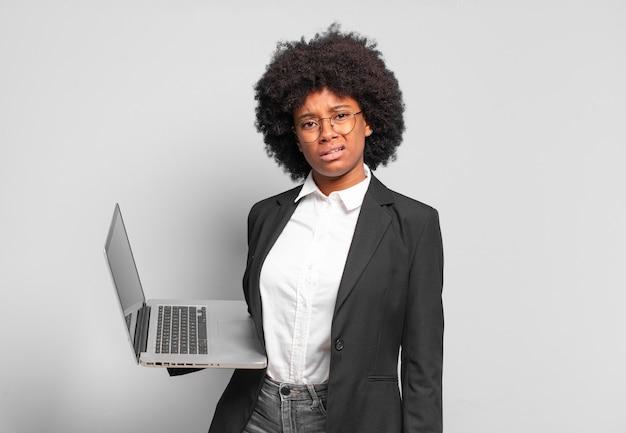 Młoda afro bizneswoman czuje się zdziwiona i zdezorientowana, z głupią, zdumioną miną, patrząc na coś nieoczekiwanego. pomysł na biznes