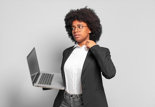Młoda afro bizneswoman czuje się zestresowana, niespokojna, zmęczona i sfrustrowana, ciągnie za szyję koszuli, wygląda na sfrustrowaną problemem.
