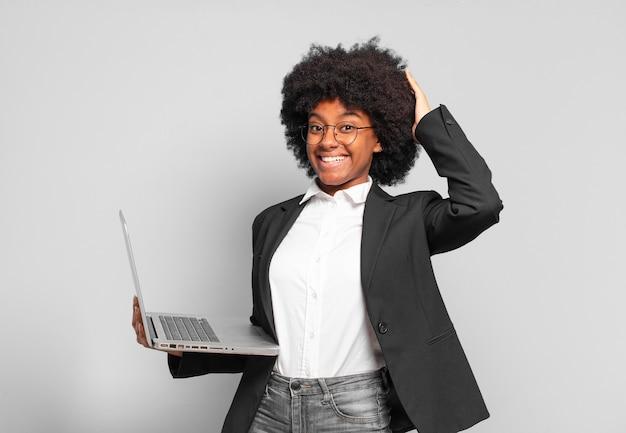 Młoda afro bizneswoman czuje się zestresowana, zmartwiona, niespokojna lub przestraszona, z rękami na głowie, panikuje z powodu pomyłki.