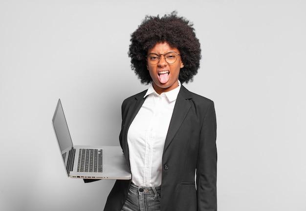 Młoda afro bizneswoman czuje się zniesmaczona i zirytowana, wystawia język, nie lubi czegoś paskudnego i obrzydliwego.