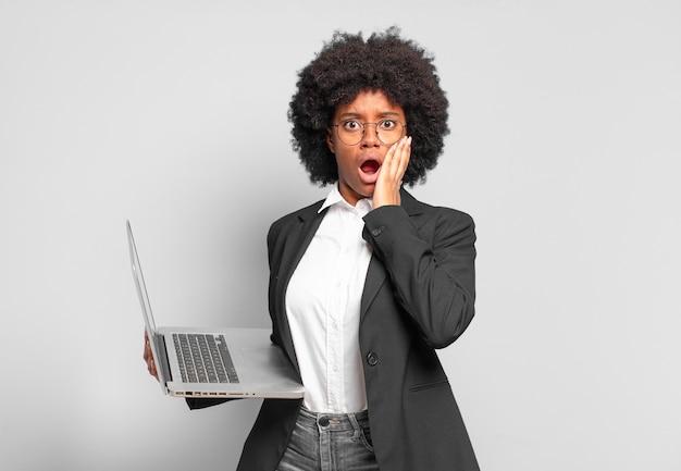 Młoda afro bizneswoman czuje się zszokowana i przestraszona, wygląda na przerażoną z otwartymi ustami i rękami na policzkach.