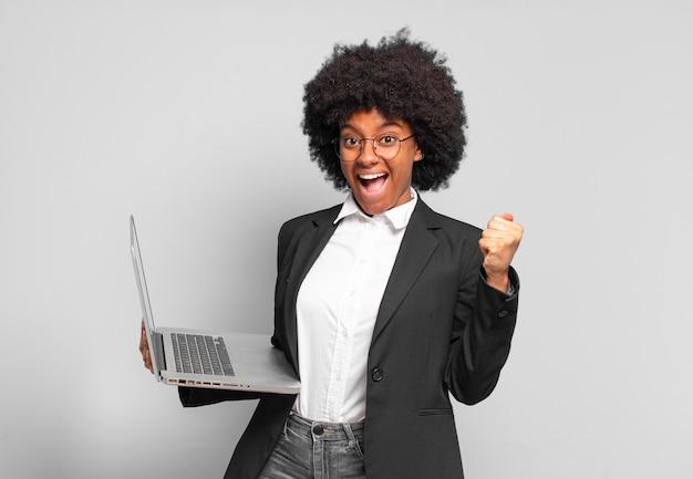 Młoda afro bizneswoman czuje się zszokowana, podekscytowana i szczęśliwa, śmiejąca się i świętująca sukces, mówiąc wow !. pomysł na biznes