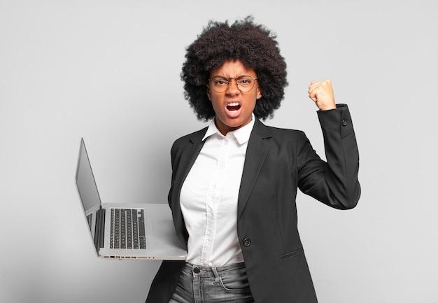 Młoda afro bizneswoman krzyczy agresywnie z gniewnym wyrazem twarzy lub z zaciśniętymi pięściami świętując sukces. pomysł na biznes