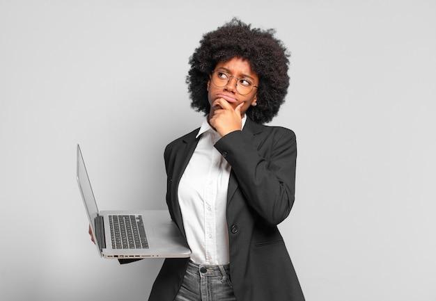 Młoda afro bizneswoman myśli, czuje się zwątpienie i zdezorientowana, z różnymi opcjami, zastanawiając się, którą decyzję podjąć. pomysł na biznes