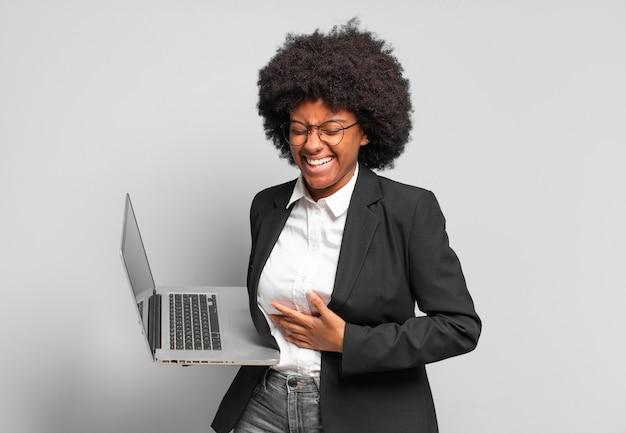 Młoda afro bizneswoman śmiejąca się głośno z jakiegoś przezabawnego żartu, szczęśliwa i wesoła, dobrze się bawiąca. pomysł na biznes