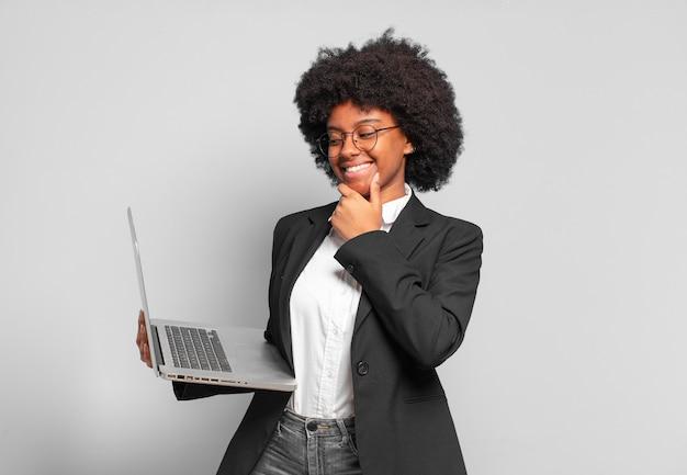 Młoda afro bizneswoman uśmiechnięta ze szczęśliwym, pewnym siebie wyrazem twarzy z ręką na brodzie, zastanawiająca się i patrząca w bok. pomysł na biznes