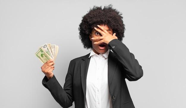 Młoda afro bizneswoman wygląda na zszokowaną, przestraszoną lub przerażoną, zakrywając twarz dłonią i zerkając między palcami. pomysł na biznes