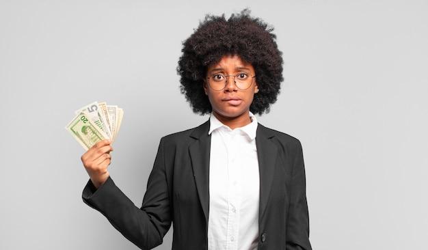 Młoda afro bizneswoman wyglądająca na zdziwioną i zdezorientowaną, przygryzając wargę nerwowym gestem, nie znając odpowiedzi na problem. pomysł na biznes