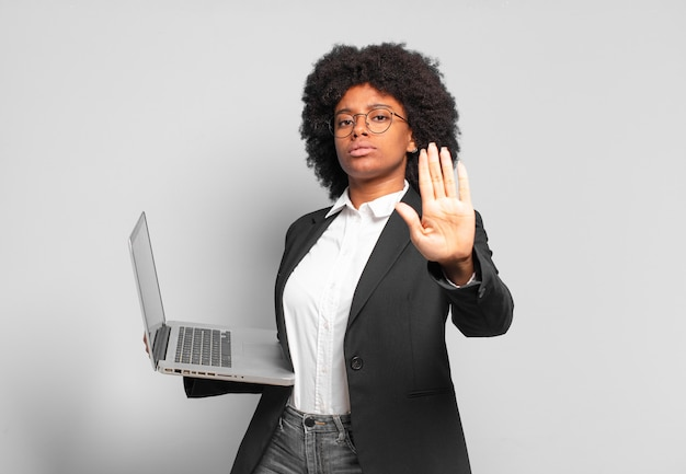Młoda afro bizneswoman wyglądająca poważnie, surowo, niezadowolona i zła, pokazując otwartą dłoń, wykonując gest zatrzymania