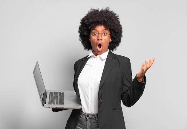 Młoda afro bizneswoman z otwartymi ustami i zdumiona, zszokowana i zdumiona niewiarygodną niespodzianką. pomysł na biznes