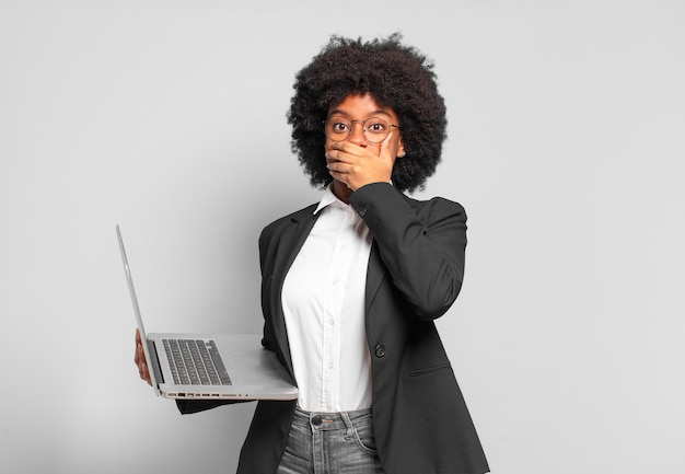 """Młoda afro bizneswoman zakrywająca usta rękami z zszokowanym, zdziwionym wyrazem twarzy, dochowująca tajemnicy lub mówiąca """"ups"""""""