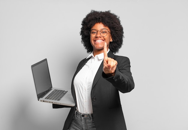 Młoda afro businesswoman uśmiechnięta dumnie i pewnie w triumfującej pozie numer jeden, czując się jak lider