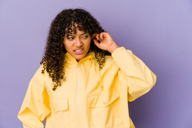 Młoda afro kobieta afro na białym tle obejmujące uszy rękami