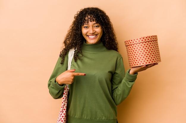 Młoda afro kobieta afroamerykanów gospodarstwa osoba prezent walentynki, wskazując ręką na przestrzeni kopii koszuli, dumny i pewny siebie