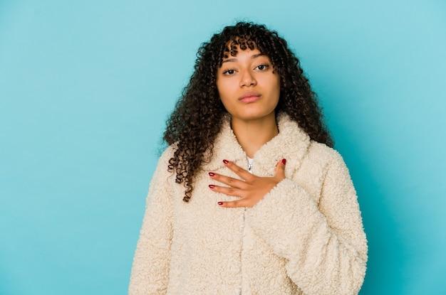 Młoda afro kobieta afroamerykanów na białym tle, składając przysięgę, kładąc rękę na klatce piersiowej.