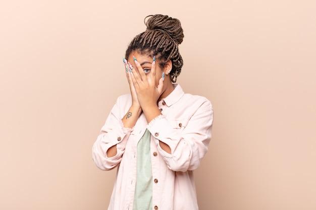 Młoda afro kobieta czuje się przestraszona lub zawstydzona, zerkająca lub szpiegująca z oczami do połowy zakrytymi rękami