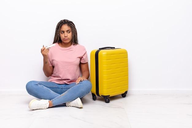 Młoda afro kobieta czuje się smutna, zdenerwowana lub zła i patrzy w bok z negatywnym nastawieniem, marszcząc brwi z powodu sprzeciwu. koncepcja wakacji
