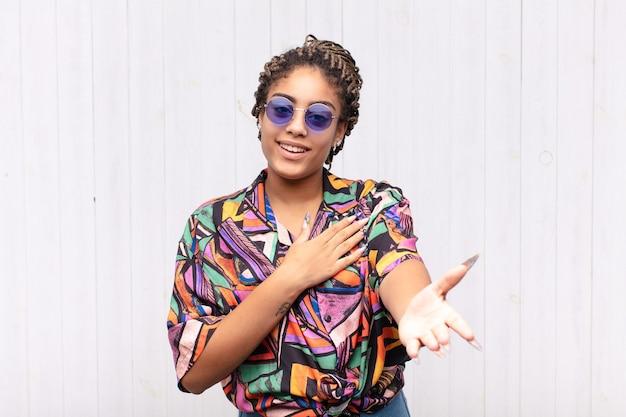 Młoda afro kobieta czuje się szczęśliwa i zakochana, uśmiecha się z jedną ręką obok serca, a drugą wyciągniętą do przodu