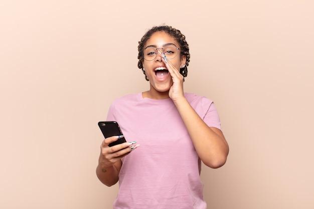 Młoda afro kobieta czuje się szczęśliwa, podekscytowana i pozytywna, wydając wielki okrzyk z rękami przy ustach, wołając. inteligentny telefon