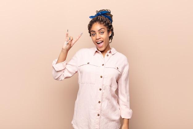 Młoda afro kobieta czuje się szczęśliwa, zabawna, pewna siebie, pozytywna i zbuntowana, robi ręką rockowy lub heavy metalowy znak
