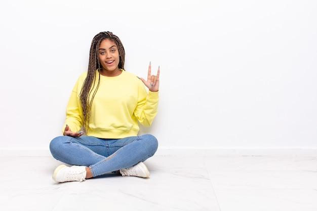 Młoda afro kobieta czuje się szczęśliwa, zabawna, pewna siebie, pozytywna i zbuntowana