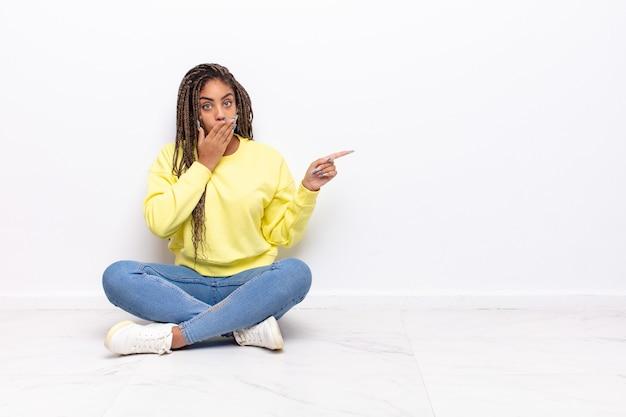 Młoda afro kobieta czuje się szczęśliwa, zszokowana i zaskoczona, zakrywająca usta dłonią i wskazująca na boczną przestrzeń kopii