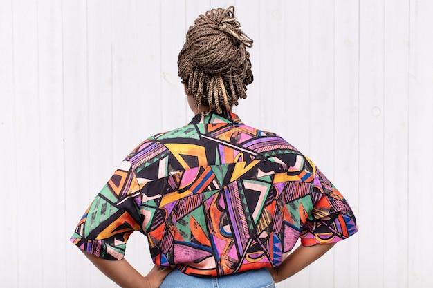Młoda afro kobieta czuje się zagubiona lub pełna lub ma wątpliwości i pytania, zastanawia się, z rękami na biodrach, widok z tyłu
