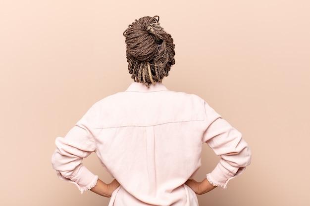Młoda afro kobieta czuje się zagubiona lub pełna lub wątpliwości i pytania na białym tle