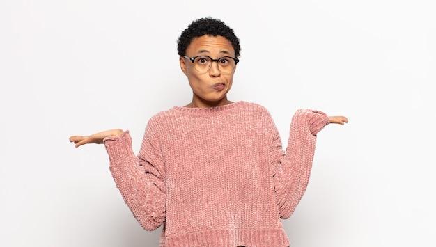 Młoda afro kobieta czuje się zakłopotana i zdezorientowana, wątpi, waży lub wybiera różne opcje ze śmiesznym wyrazem twarzy