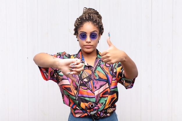 Młoda afro kobieta czuje się zdezorientowana, nieświadoma i niepewna, ważąc dobro i zło w różnych opcjach lub wyborach
