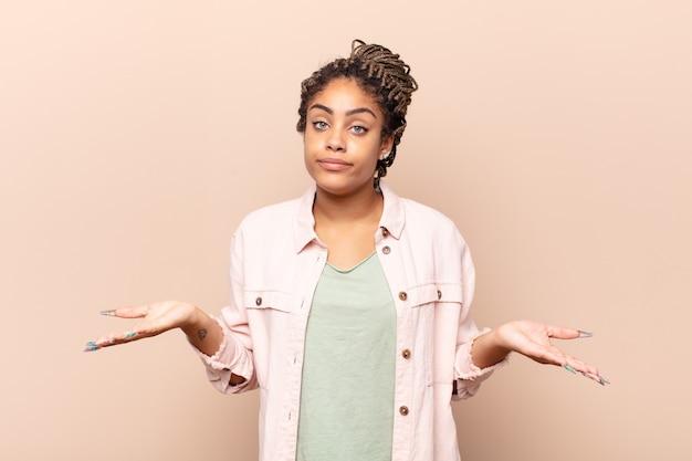 Młoda afro kobieta czuje się zdziwiona i zdezorientowana, niepewna właściwej odpowiedzi lub decyzji, próbująca dokonać wyboru