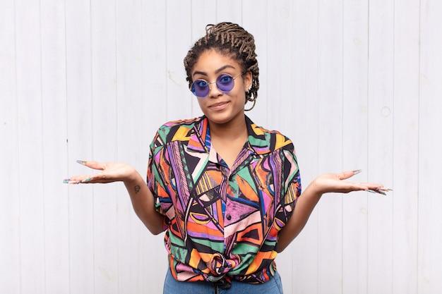 Młoda afro kobieta czuje się zdziwiona i zdezorientowana, wątpi, waży lub wybiera różne opcje z zabawnym wyrazem twarzy