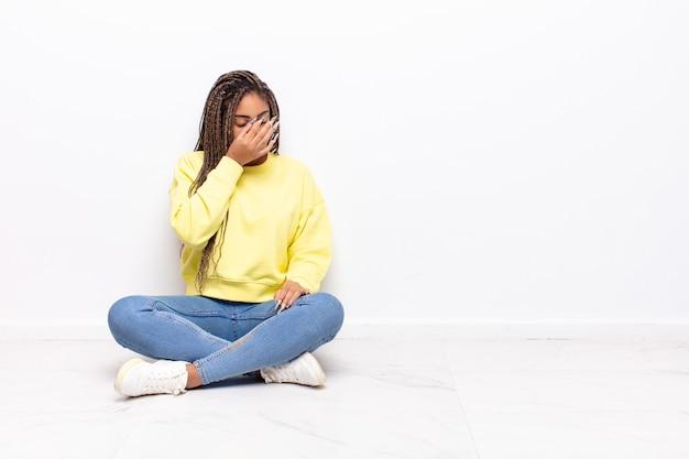 Młoda afro kobieta czuje się zestresowana, nieszczęśliwa i sfrustrowana, dotyka czoła i cierpi na migrenę lub silny ból głowy