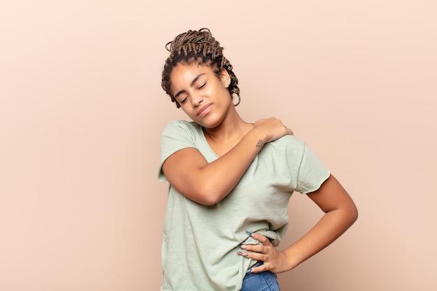 Młoda afro kobieta czuje się zmęczona, zestresowana, niespokojna, sfrustrowana i przygnębiona, cierpi na ból pleców lub szyi