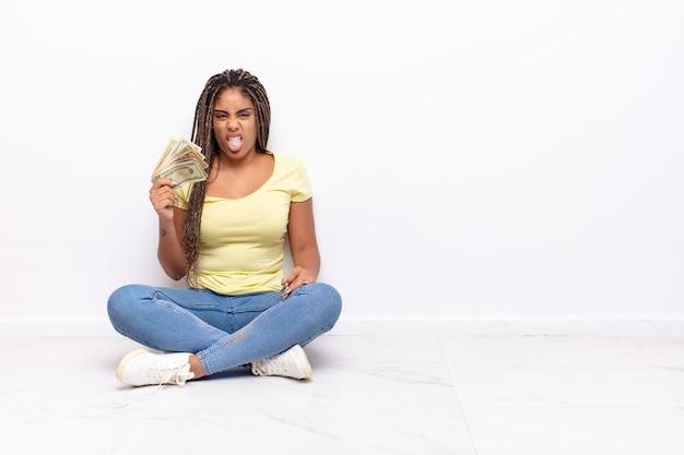 Młoda afro kobieta czuje się zniesmaczona i poirytowana, wystawia język, nie lubi czegoś paskudnego i obrzydliwego. koncepcja pieniędzy