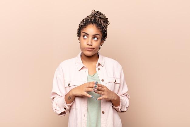 Młoda afro kobieta knuje intrygi i konspiruje, myśli podstępne sztuczki i oszustwa, przebiegłość i zdradę