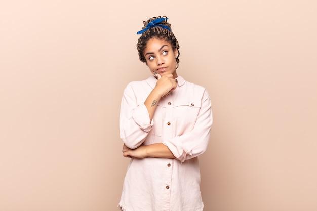Młoda afro kobieta myśli, czuje się niepewna i zdezorientowana, z różnymi opcjami