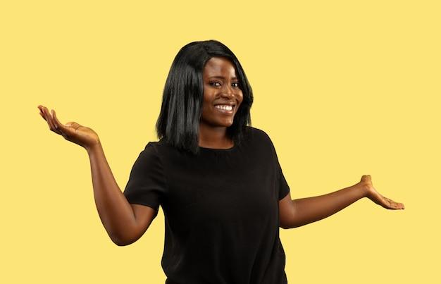Młoda afro-kobieta na białym tle na żółtej ścianie, wyraz twarzy. piękny portret kobiety w połowie długości. pojęcie ludzkich emocji, wyraz twarzy. wybieranie i zachęcanie.