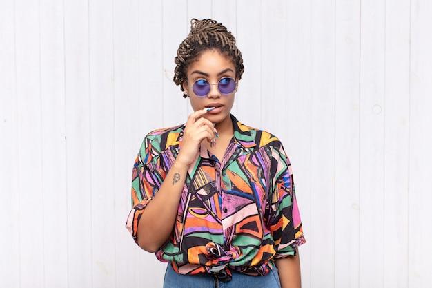 Młoda afro kobieta o spojrzeniu zdziwionym, nerwowym, zmartwionym lub przestraszonym, spoglądająca w bok w kierunku miejsca na kopię