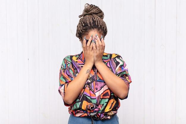 Młoda afro kobieta smutna, sfrustrowana, zdenerwowana i przygnębiona, zakrywająca twarz obiema rękami, płacząca