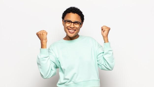 Młoda afro kobieta świętująca niewiarygodny sukces jak zwycięzca